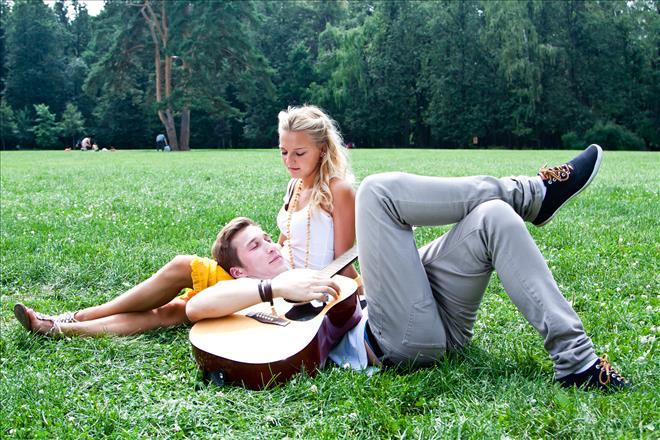 Man playing guitar to girl