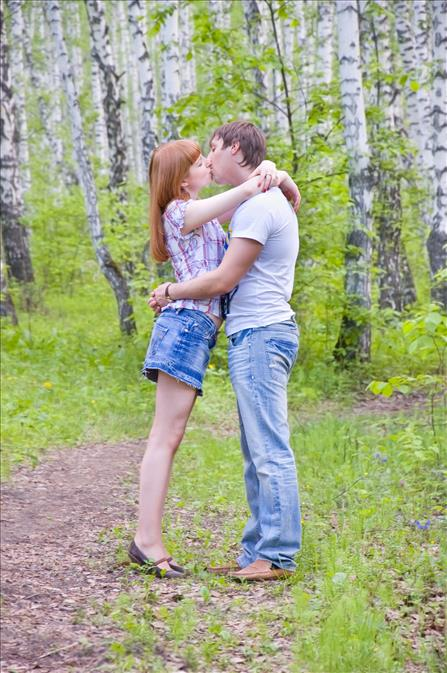 couple kissing on hike in woods